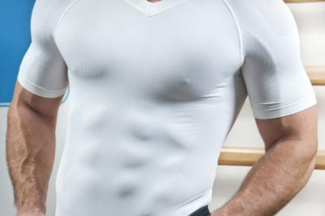 Muscular torso through white shirt in gym.