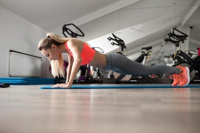 Woman make push-ups in gym