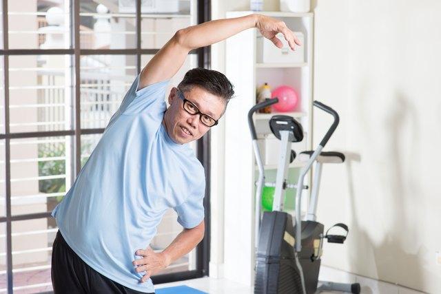 Mature Asian man arms stretching at gym