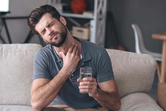 Frustrated young man touches his neck while holding a glass of water