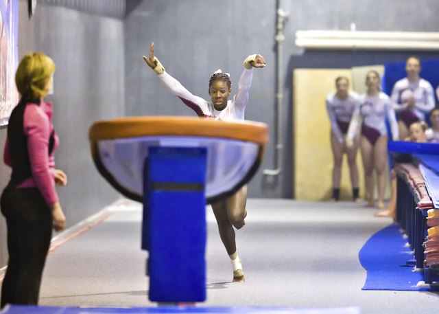 Teammates and Coach Watch Gymnast Performing Vault