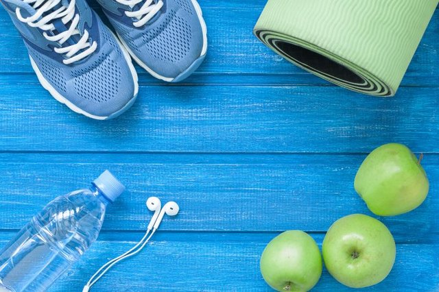 Flat lay sport shoes, bottle of water, mat and earphones on blue wooden background. Concept healthy lifestyle, sport and diet. Selective focus.