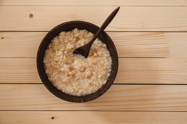 Bowl of hot oatmeal with wooden spoon on the table
