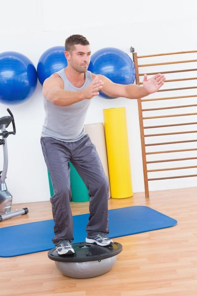 Concentrate man training in bosu ball in fitness studio