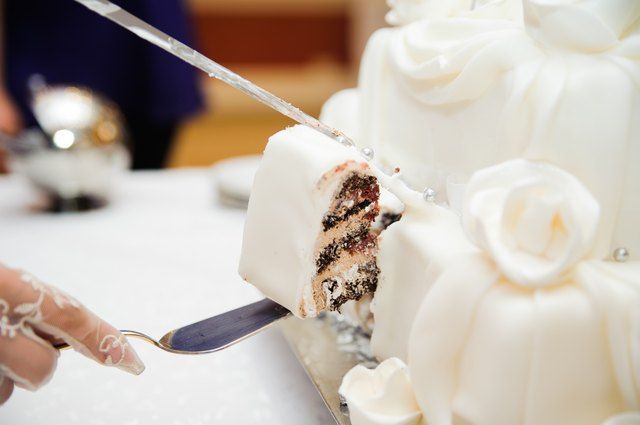 bride and groom are Slicing the wedding cake on reception