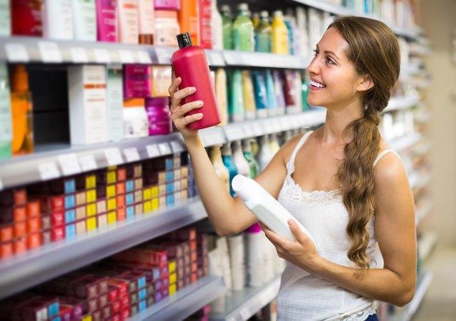 Woman choosing shampoo at store