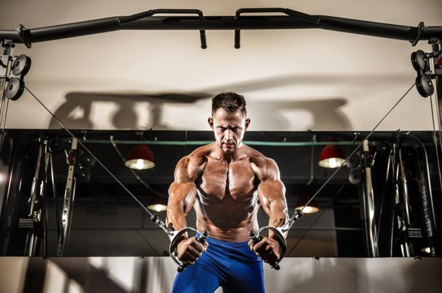 Young Bodybuilder Is Working On His Chest With Cable Crossover In Gym