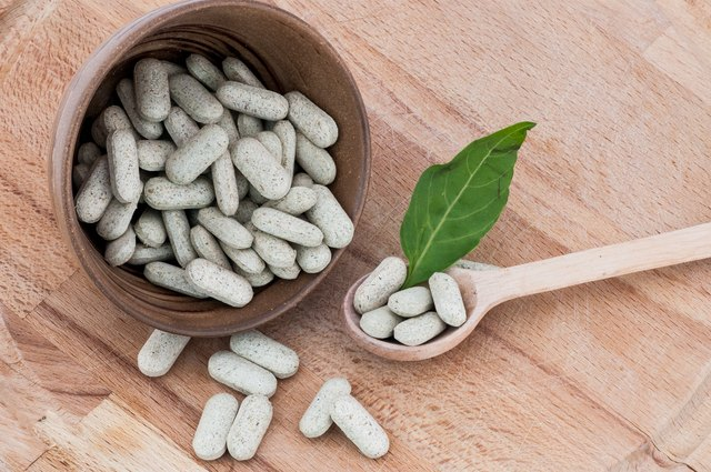 Alternative pills on a wooden spoon and in a bowl