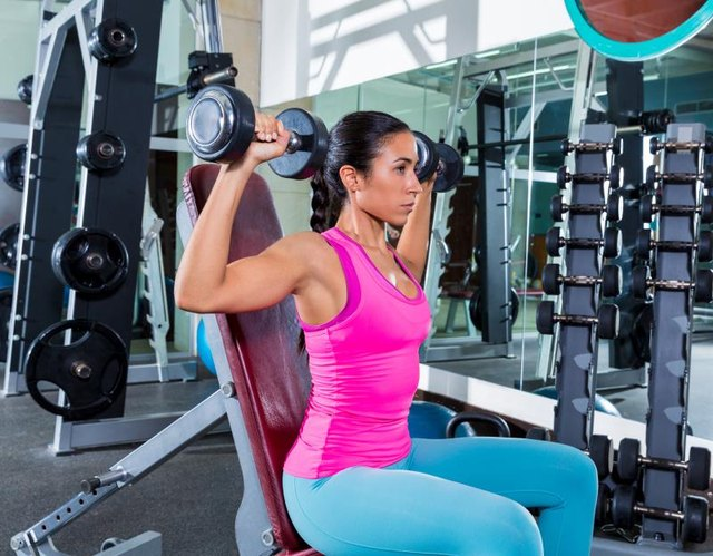 girl at gym seated dumbbell shoulder press workout exercise