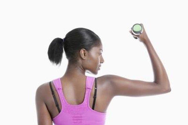 Back view of young woman raising dumbbell over white background