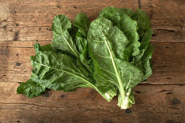 bunch of fresh spinach on wooden table