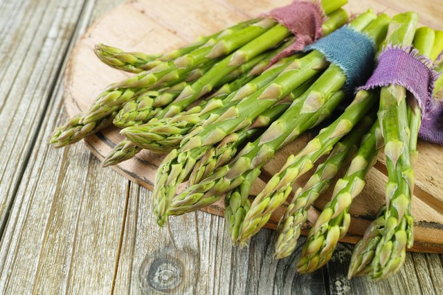 Bunch of fresh green asparagus on wooden table