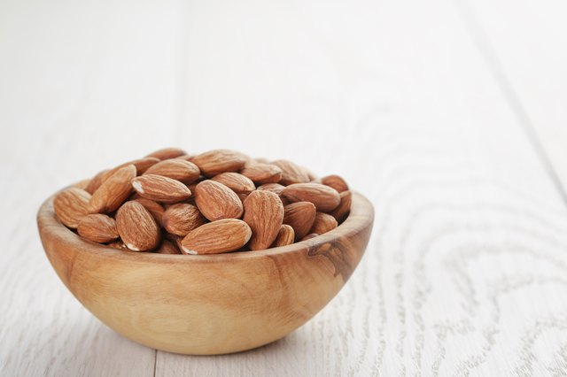 roasted almonds in bowl on white wooden table