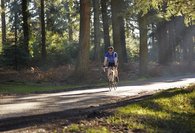 Cyclist riding on road through forest