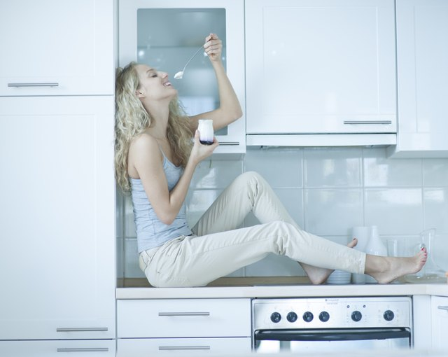 Young woman eating yogurt while sitting on kitchen counter