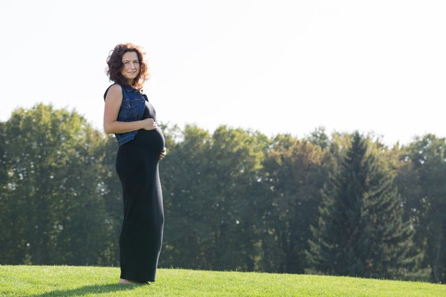Pregnant woman is standing on the green lawn.