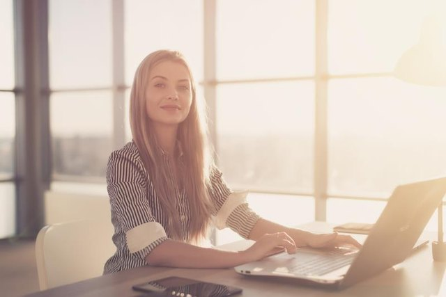 Woman blogging in spacious office using computer on her workplace. Female employee sitting, smiling, looking at camera