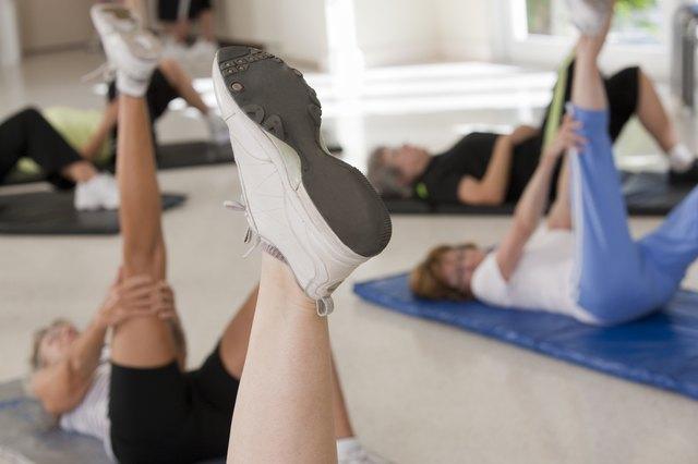 Seniors on floor mats doing let exercises