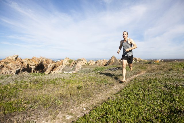 Male athlete running barefoot and fast on a walking trail
