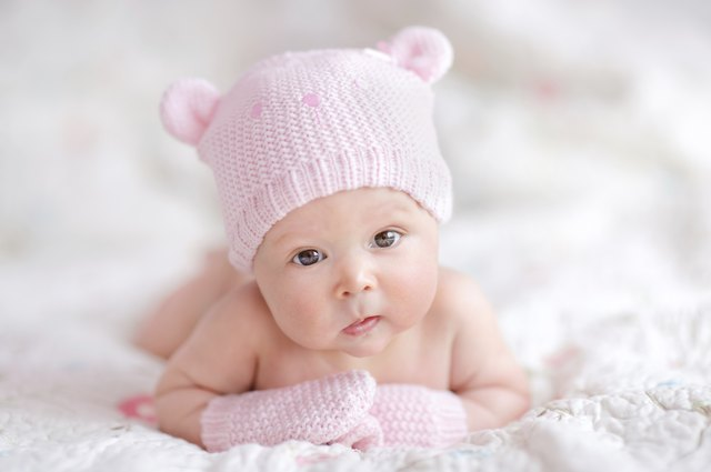 newborn baby girl in pink knitted bear hat