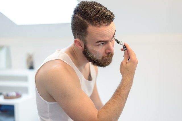 Young man shaving above his beard