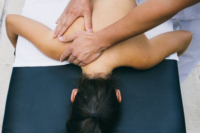 Physiotherapist massaging the shoulders of a patient