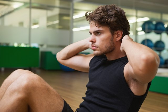 Fit handsome man doing sit ups in fitness studio