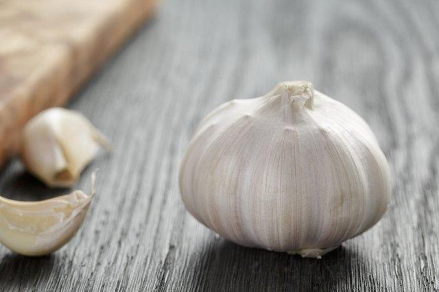 whole garlic head on oak wood table