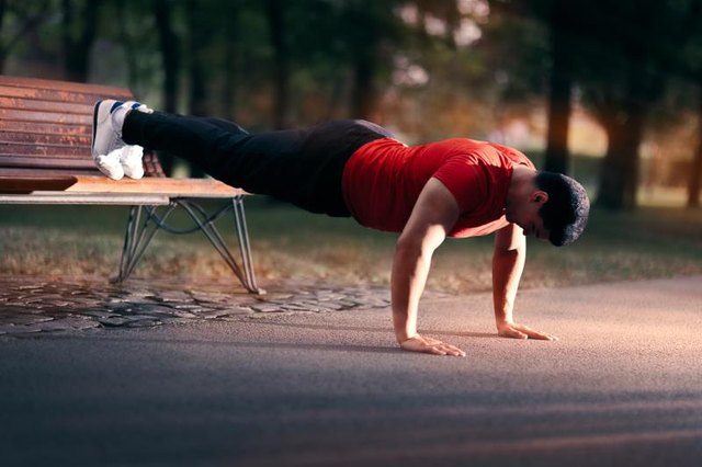 Athletic guy doing push-ups with his fit on a bench