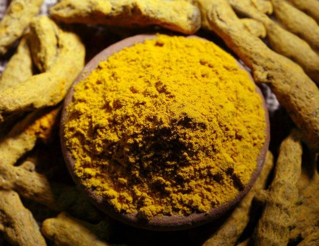 Top angle view of turmeric powder and dry turmeric
