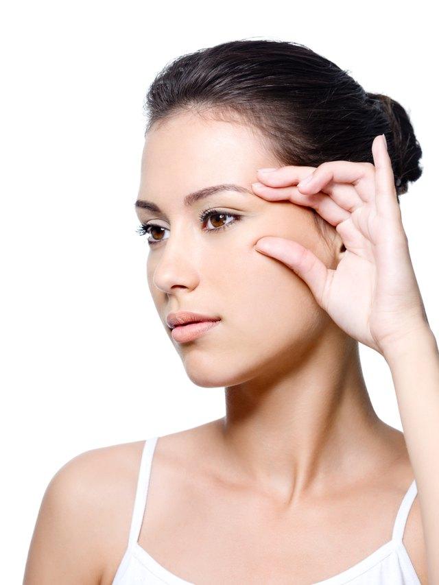 Woman pinching skin near her eye
