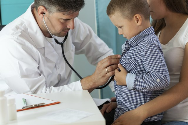 Pediatrician examining boy lungs