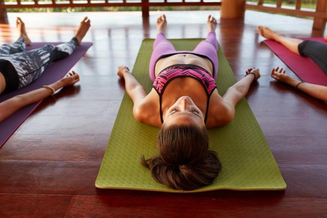 Shot of women at yoga class doing savasana, lying on exercise mat. Young people relaxing at yoga class.