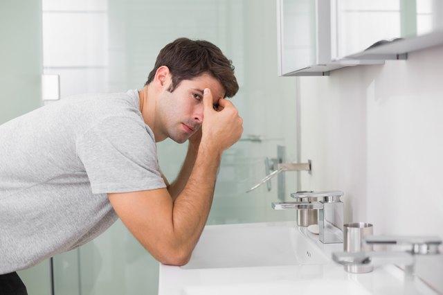 Tensed young man at washbasin in bathroom
