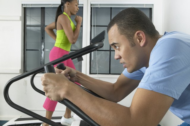 Young man and a young woman exercising on treadmills