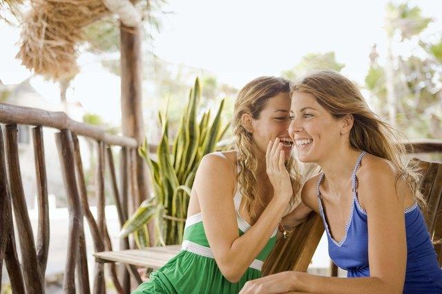 Women whispering outdoors
