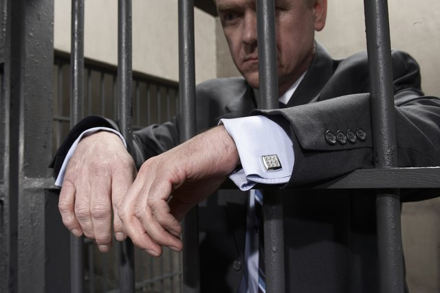 Man standing behind bars in prison cell, close-up of hands