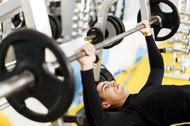 A young man prepares for a standard barbell bench press on a flat bench.