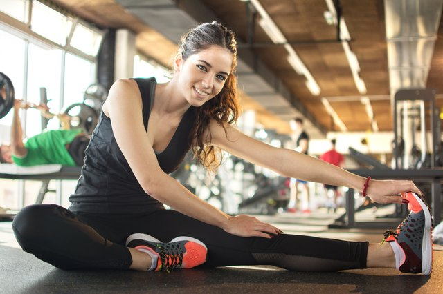 Smiling sporty woman stretching at gym.