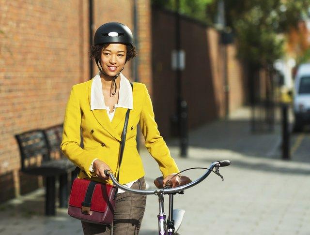 Young women pushing her bike in the city