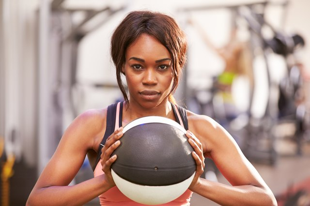 Portrait of a woman holding a medicine ball at gym