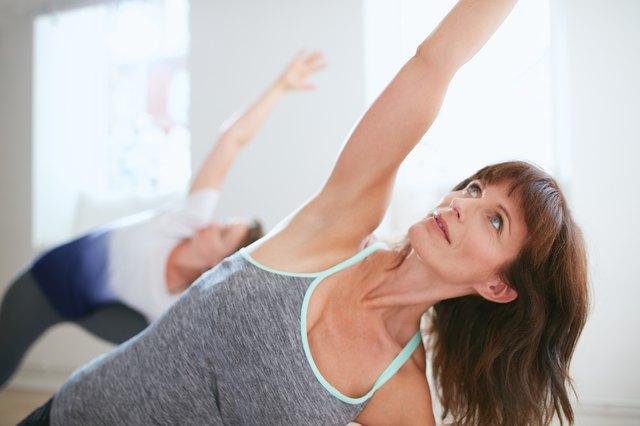 Fitness trainer doing Trikonasana pose at yoga class