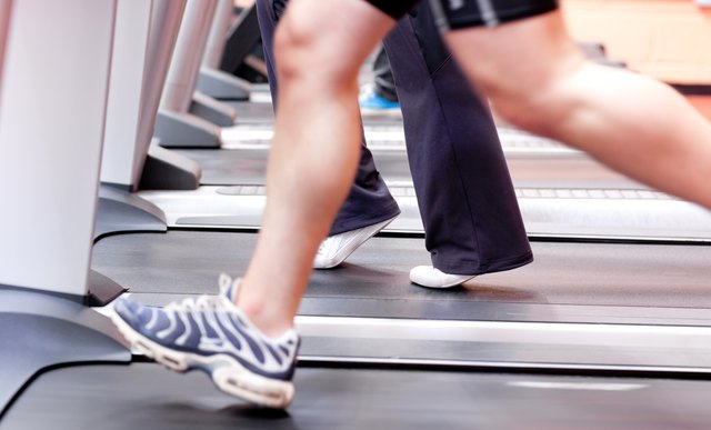Close-up of the legs of an athletic young woman exercising on a running machine