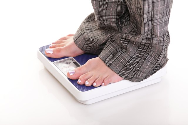 Woman feet and weight scale on white background