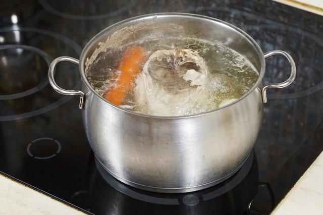 simmering chicken soup with seasoning vegetables