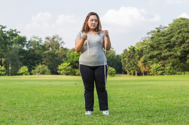 Obese woman is worrying about her overweight.