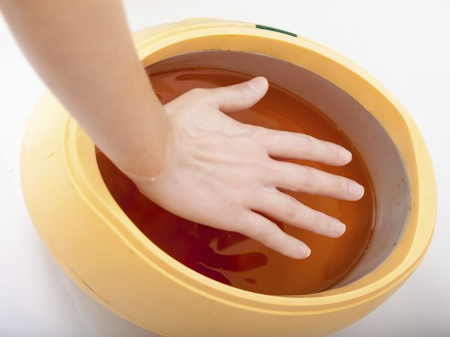 Female hand orange paraffin wax bowl. Manicure beauty spa salon