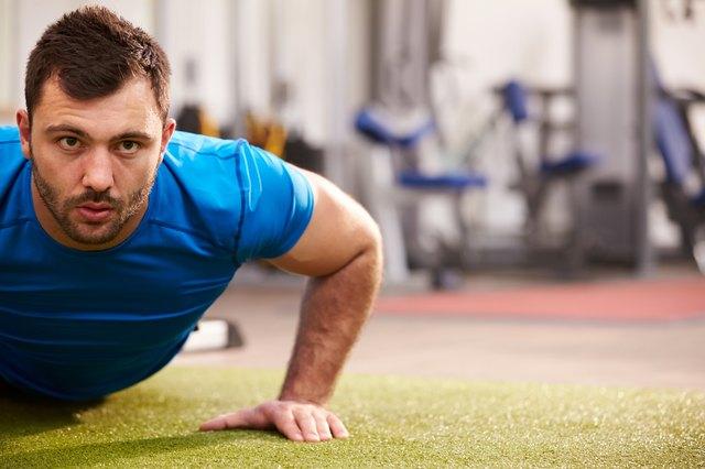 Young man doing push ups at a gym