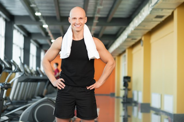 Athletic guy with towel on gym