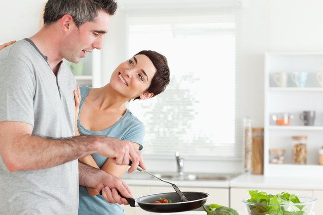 Woman smiling at her pan-holding husband